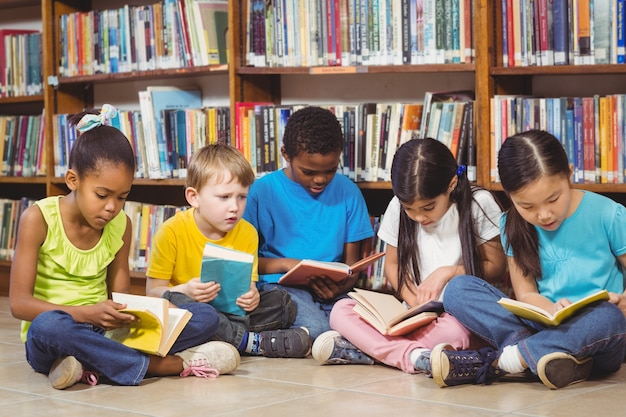 Alunni seduti per terra e leggendo libri in biblioteca