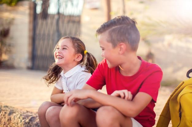 Alunni sorridenti seduti insieme all'aperto. concetto di bambini ed emozioni.