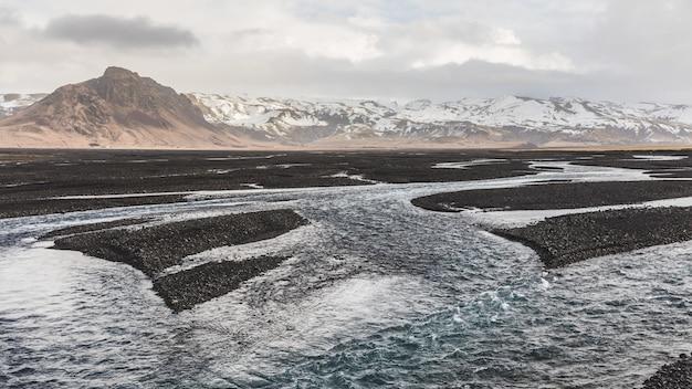 Alveo roccioso e ruscello con montagne
