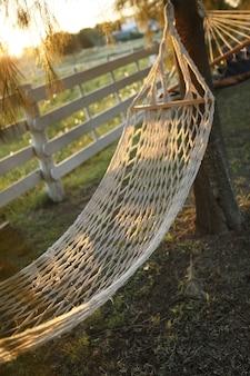 Amaca della fibra vegetale al tramonto dorato nel campo