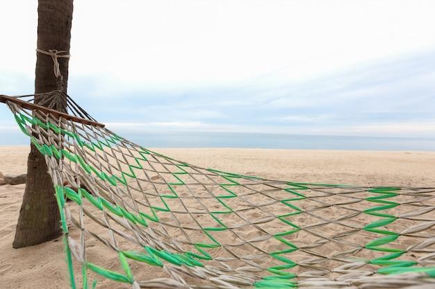 Amaca su un tramonto di palma abbagliamento del sole mare oceano cielo riva sabbia