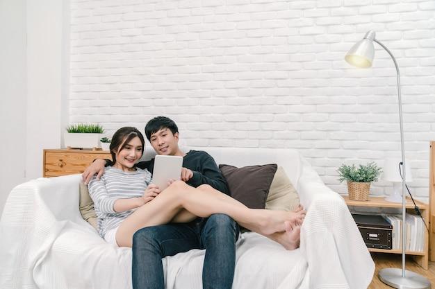 Amante asiatico felice che si siede e che utilizza la compressa di tecnologia digitale per selfie sopra il sofà