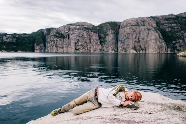 Amante della natura. equipaggi il sonno sulla roccia del fiordo della norvegia nel giorno di estate.