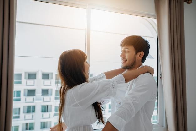 Amante delle coppie che mette su felicità della stanza del letto stile di vita e ragazza sorridente che si rilassano nel letto bianco