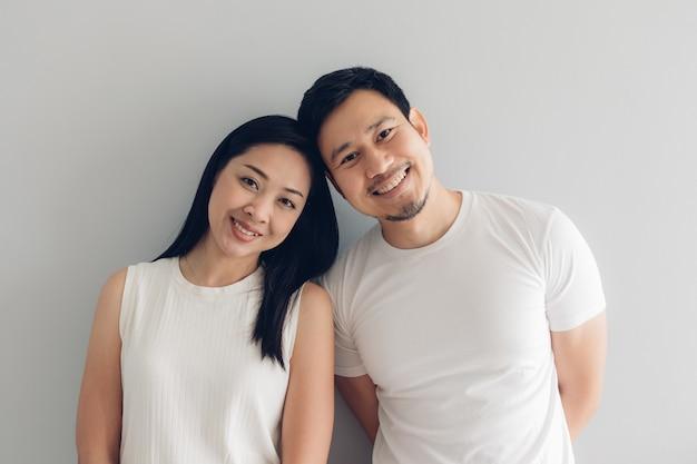 Amante di coppia felice in t-shirt bianca e sfondo grigio.