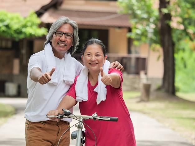 Amante senior delle coppie che cicla nella casa del parco
