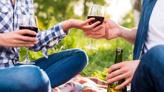 Amanti anonimi che danno un bicchiere di vino a vicenda