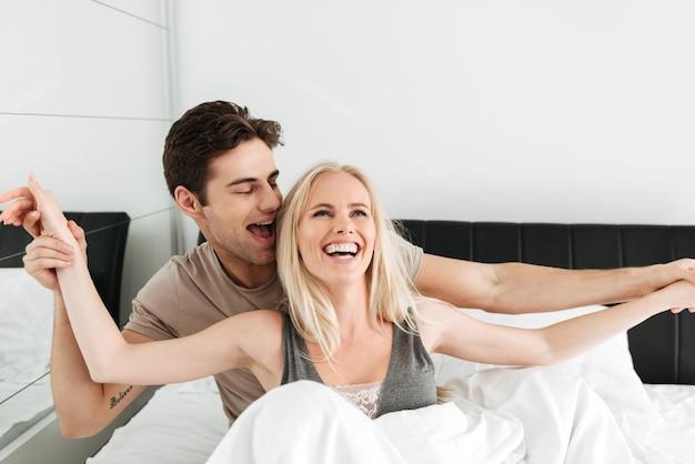 Amanti divertenti allegri che abbracciano a letto e che ridono