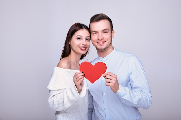 Amanti felici con cuore di carta rosso.