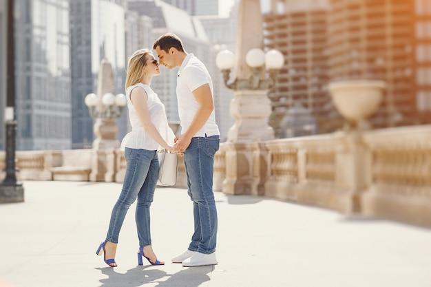 Amanti giovani ed eleganti coppia in magliette bianche e blue jeans camminando in una grande città