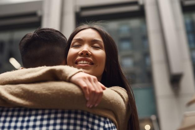 Amanti teenager felici romantici che abbracciano al paesaggio urbano.