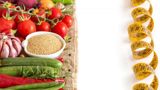 Amaranto organico crudo e verdure crude isolati sulla fine di bianco su