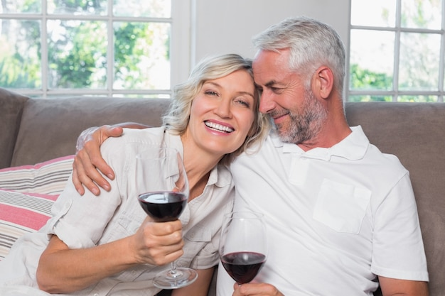 Amare la coppia matura con bicchieri di vino nel salotto