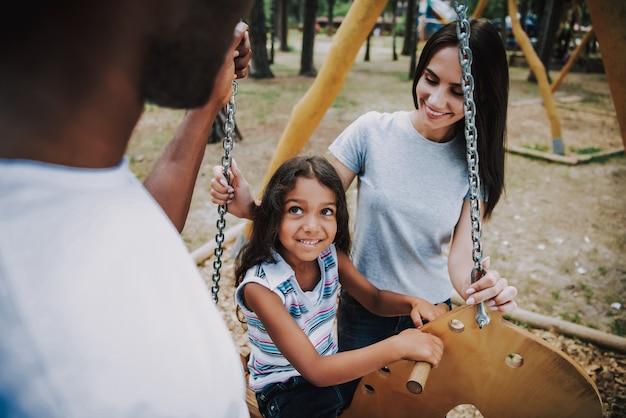Amare mamma e papà figlia oscillante nel parco