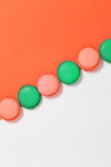 Amaretti colorati dolci in fila. i biscotti luminosi del maccherone si chiudono su su fondo di carta.
