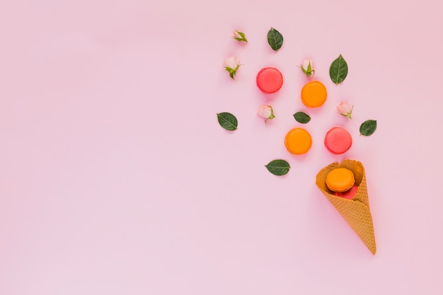 Amaretti colorati; rosa; e foglie disposte sopra il cono della cialda su sfondo rosa