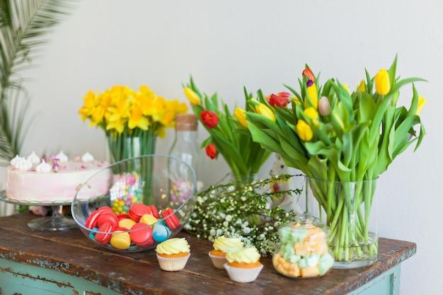 Amaretti luminosi e cupcakes su un tavolo di legno. colpo di luce naturale all'interno con una piccola profondità di campo