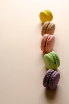 Amaretti multicolori in fila su beige pastello.