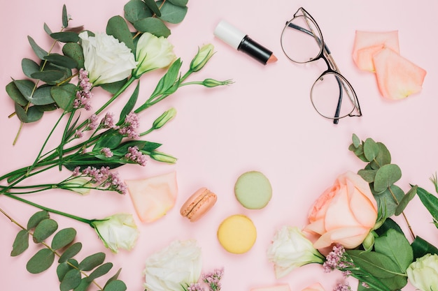 Amaretti; rossetto; occhiali con rosa; limonium e fiori eustoma su sfondo rosa