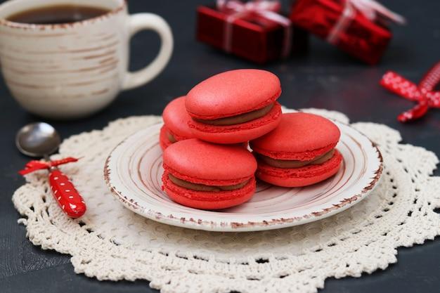 Amaretti rossi e tazza di caffè si trovano su un piatto su uno sfondo scuro