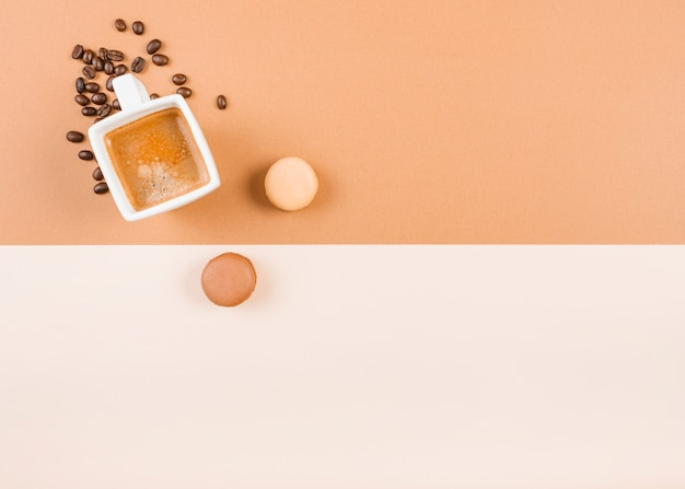 Amaretti; tazza di caffè; e chicchi di caffè tostato su doppio fondo