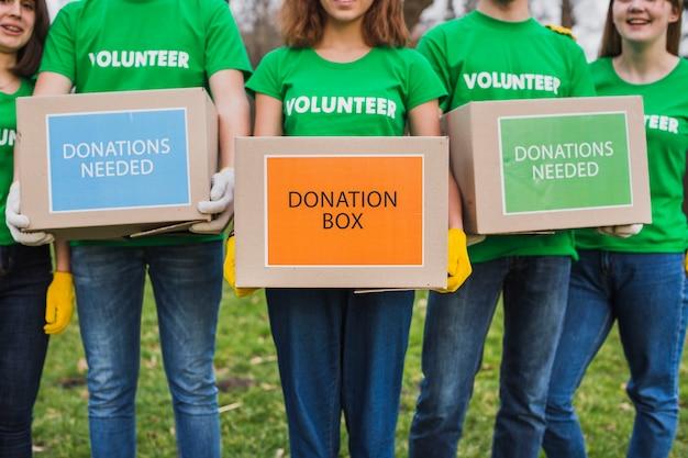 Ambiente e concetto di volontariato con persone che tengono le scatole per le donazioni