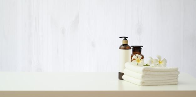 Ambiente termale con fiori di plumeria e bottiglia di olio essenziale