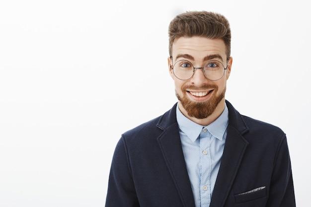 Ambizioso giovane uomo d'affari alla moda intelligente e creativo in occhiali rotondi con barba e occhi azzurri in piedi in abito alla moda che sorride ampiamente sentendosi stupito ed entusiasta di iniziare un nuovo progetto