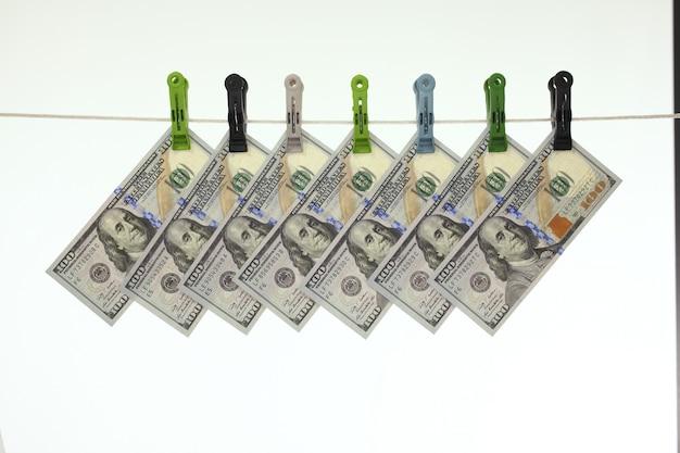 Americano 100 dollari di banconote in una corda da bucato - riciclaggio di denaro - concetto sporco dei soldi - isolato