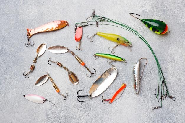 Ami ed esche da pesca in un insieme per la pesca del pesce differente su una tavola grigia con lo spazio della copia. disteso