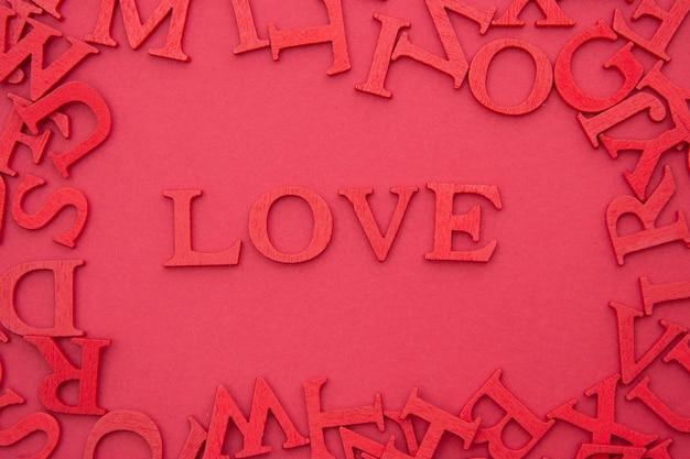 Ami l'iscrizione, lettere rosse di legno 3d su fondo rosso. san valentino creativo