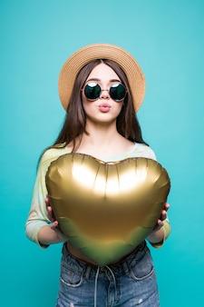 Ami la donna sorridente che tiene palloncino a forma di cuore dorato. bella giovane donna sveglia nell'amore isolato sul verde