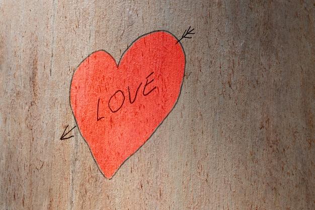 Ami la mano del cuore e ami il testo dipinto su un albero del tronco. amore