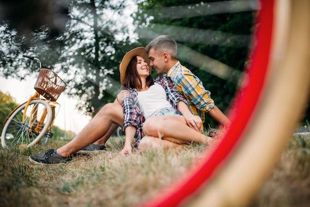 Ami le coppie con le bici dell'annata che si siedono sull'erba