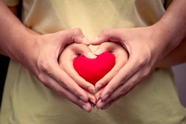 Ami le mani delle coppie con cuore rosso nel tono di colore dell'annata