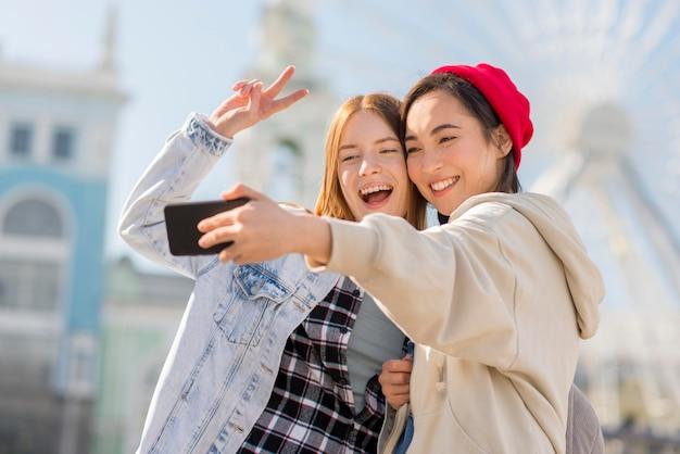 Amiche che prendono selfie con l'occhio di londra