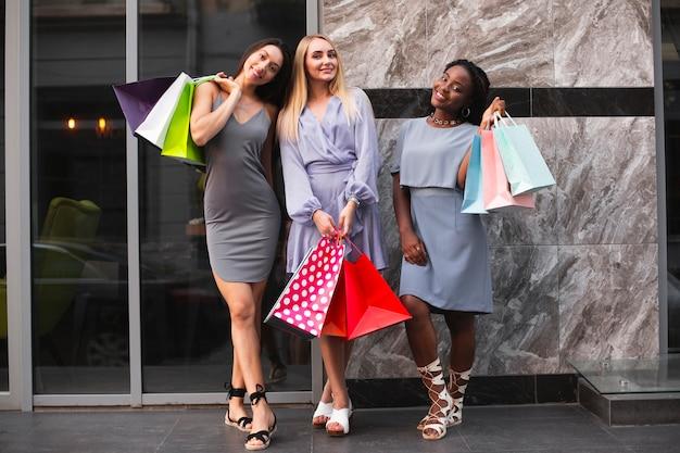 Amiche che tengono i sacchetti con lo shopping di abbigliamento