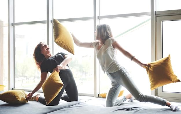 Amiche divertenti giocano a cuscini, vicino a grandi finestre.