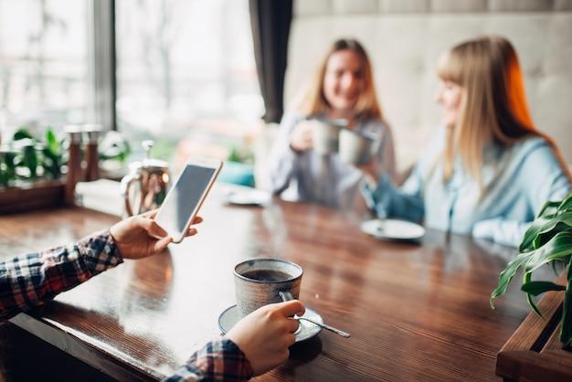 Amiche felici beve caffè nella caffetteria