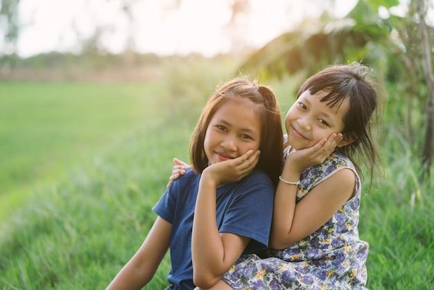 Amiche felici del piccolo bambino nel campo verde