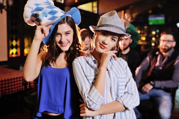 Amiche in cappelli bavaresi che sorridono allo sfondo del bar durante la celebrazione dell'oktoberfest