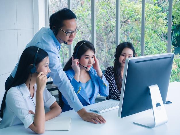 Amichevole agente team operatore con cuffie che lavorano in un call center