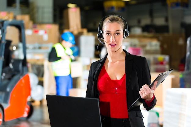 Amichevole donna, dispatcher o supervisore che utilizza l'auricolare e il laptop presso il magazzino della compagnia di spedizioni,