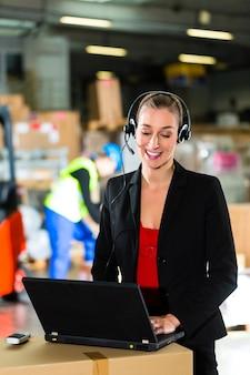 Amichevole donna, dispatcher o supervisore utilizzando l'auricolare e il laptop presso il magazzino della compagnia di spedizioni, un carrello elevatore