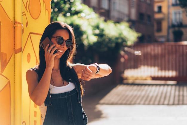 Amichevole donna parla al cellulare e guarda l'ora