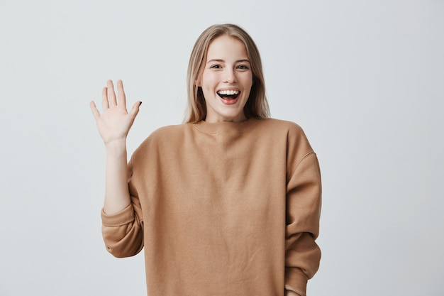 Amichevole femmina bionda positiva che sorride ampiamente e felicemente, saluta con la mano, lieta di incontrarli. emozioni, sentimenti ed espressione del viso positivi.