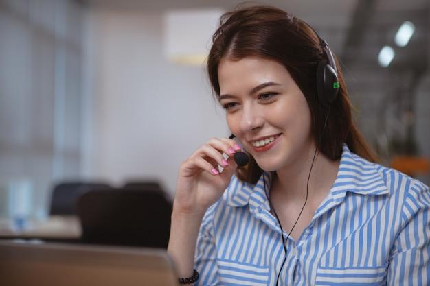Amichevole operatore del servizio clienti con cuffia che lavora al call center