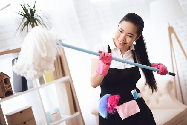 Amichevole ragazza asiatica con mop hotel housekeeper.