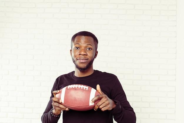 Amichevole uomo nero sorridente in possesso di un pallone da calcio