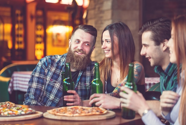 Amici a bere qualcosa in un bar, sono seduti a un tavolo di legno con birre e pizza.